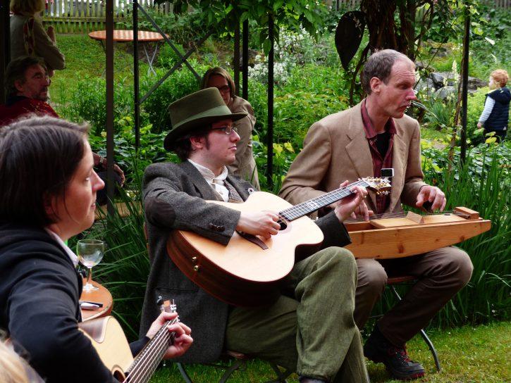 Alexandra Bücking, Sebastian Barwinek und Axel Gladrow musizieren im Garten Kölsch.